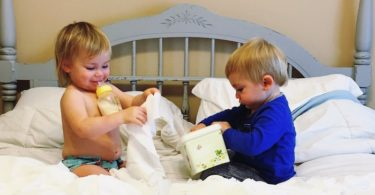 twins pulling out wipes from container on bed Keep Twins Busy
