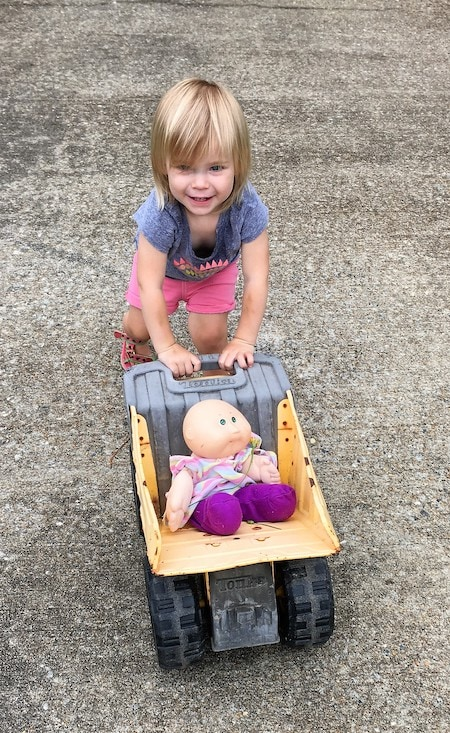 toddler girl pushing doll in a toy wagon Keep Twins Busy