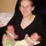 mom holding newborn twins exclusively breastfed twins