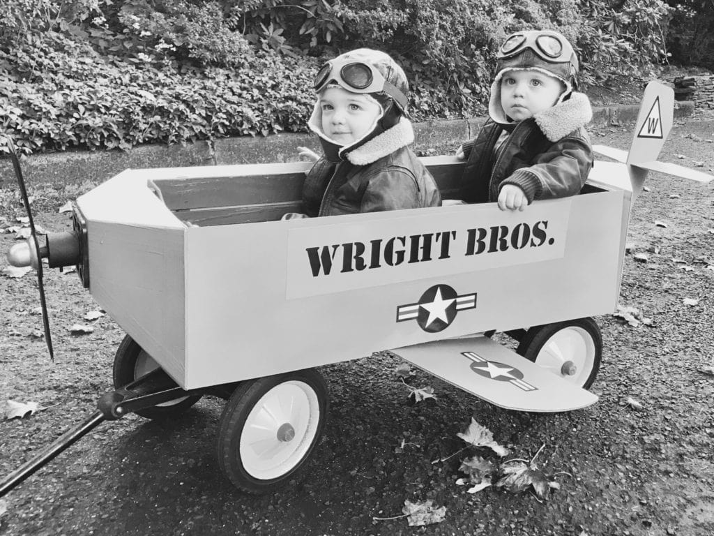 twin toddler boys dressed as the Wright brothers and sitting in a wagon decorate to look like an airplane
