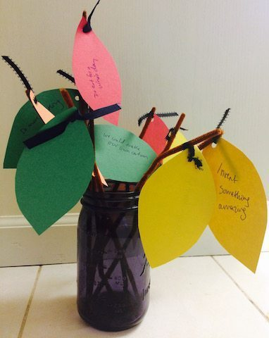 glass jar with paper leaves with written wishes New Year with Kids