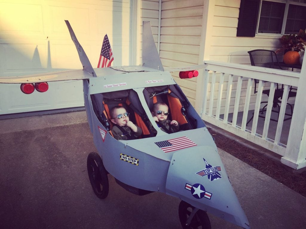 baby twin boys dressed as top gun characters in a stroller dressed up like an airplane