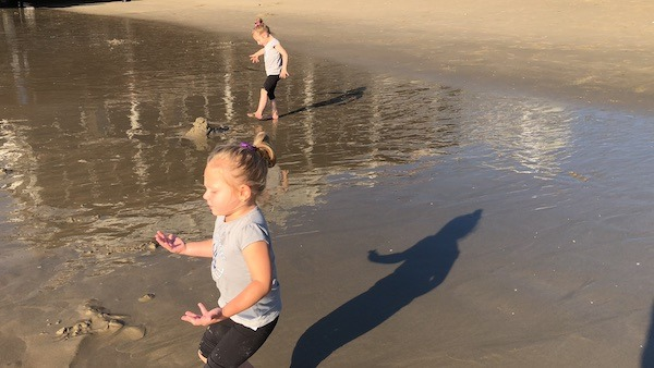 two girls playing at the beach evacuating