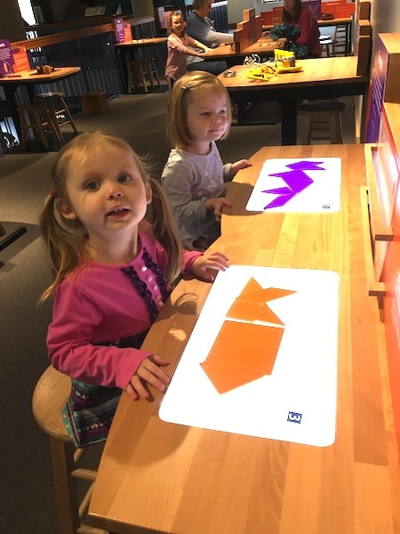 girls playing with tangrams love of math