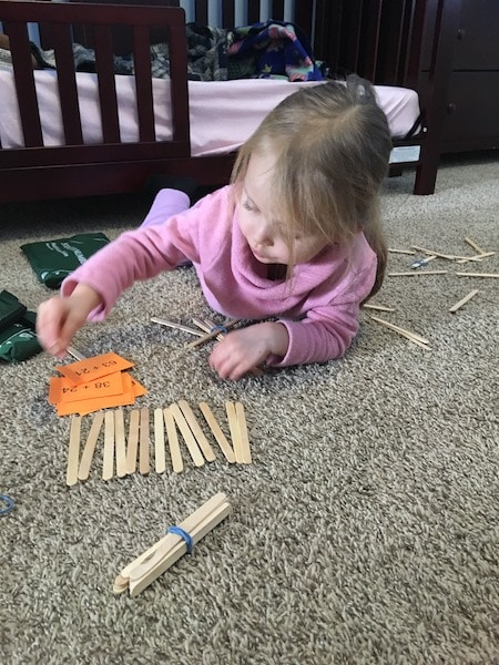 girl playing with popsicle sticks love of math