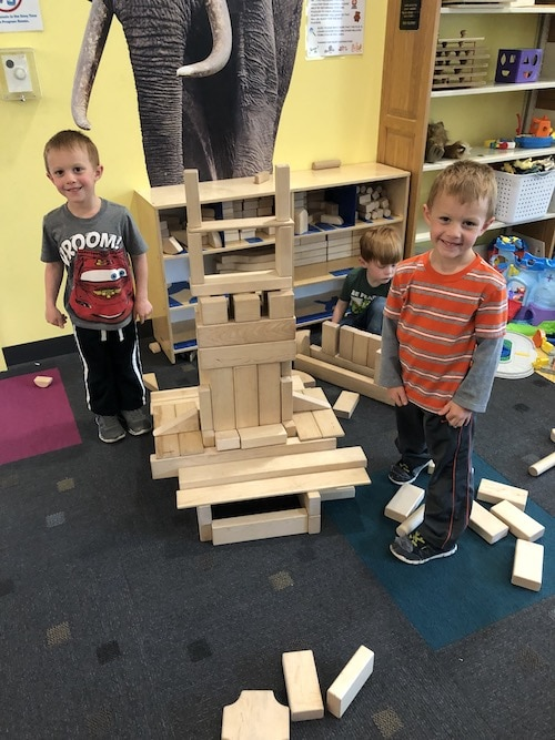 twin boys building with large wooden blocks choose toys