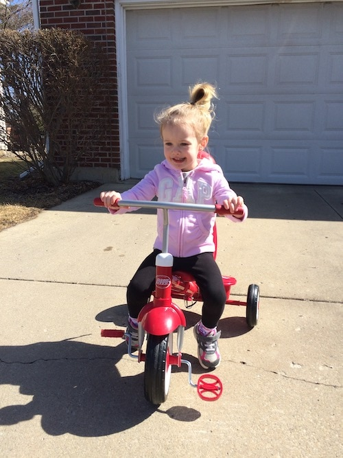 preschool girl on a tricycle choose toys