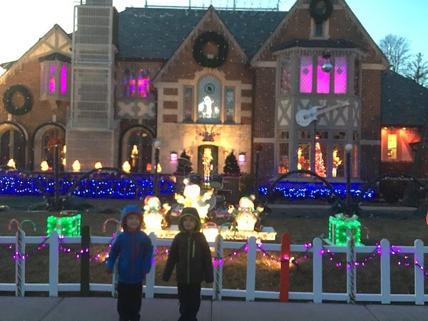 twin boys 5 years old standing in front of house with christmas lights Prince theme holiday memories