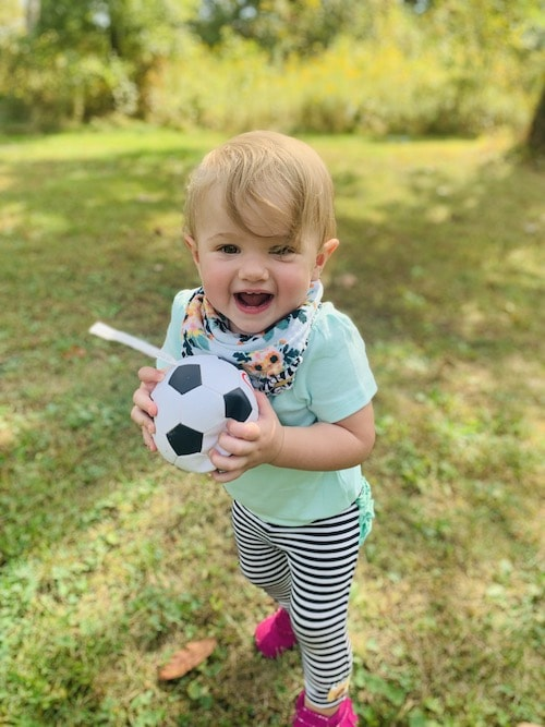 toddler girl holding small ball in backyard choose toys