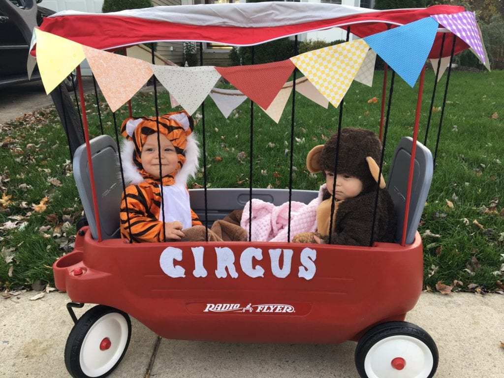 baby twin boys dressed up as a tiger and a monkey in a wagon decorated to look like a cage and it says circus on the side