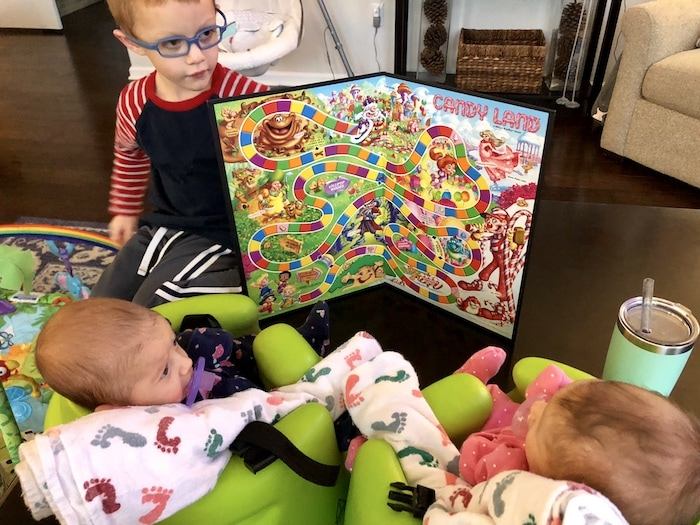 boy holding up candy land board to his infant twin sisters choose toys