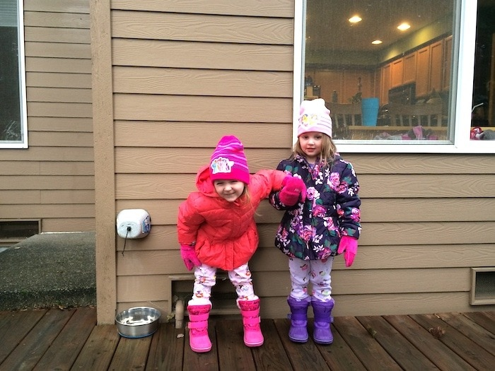 twin girls in coats outside three-year-old twins