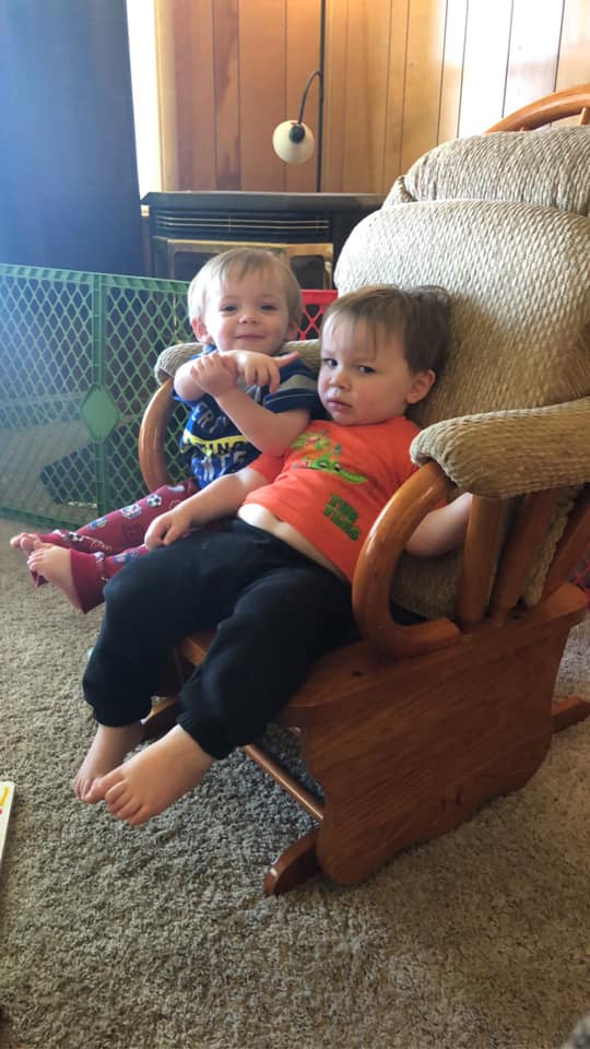 twin boys sitting in a chair why are you covered in poop