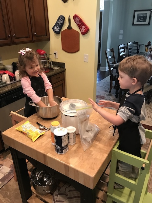 two kids cooking at a high table standing in cooking stools kids cooking