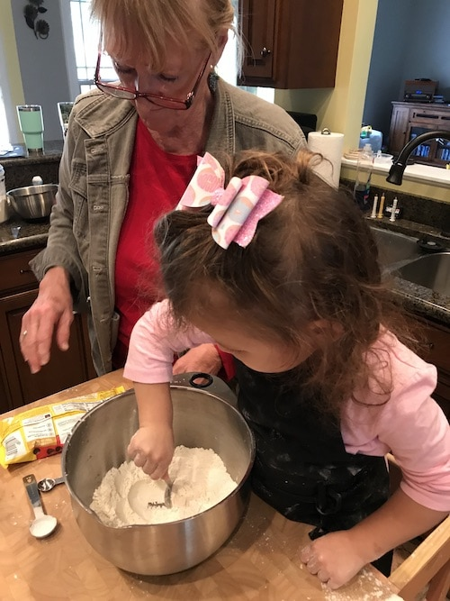 little girl scooping flour and grandma watching kids cooking