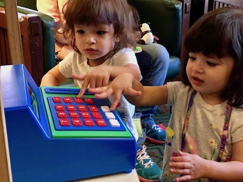 twin girls playing with cash register Sharing Between Twins
