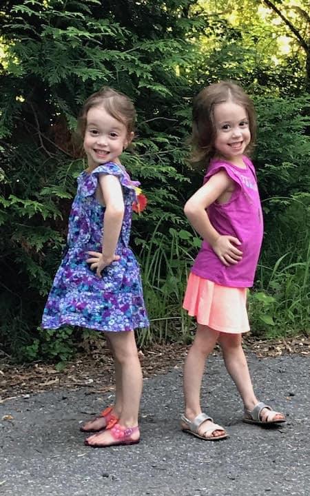 two girls preparing twins for kindergarten