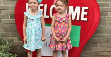 twin girls standing by school preparing twins for kindergarten