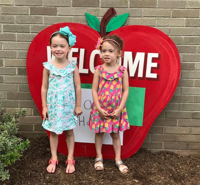 twin girls standing by school preparing twins for kindergarten