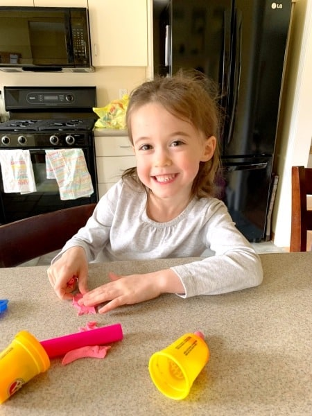 girl playing with play-doh preparing twins for kindergarten