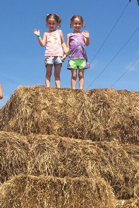 twin girls 5 years old standing on a hay bale embrace their individuality