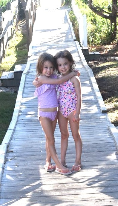 twin girls 5 years old standing on a boardwalk embrace their individuality