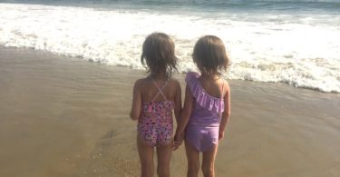 twin 5 year old girls on a beach embrace their individuality