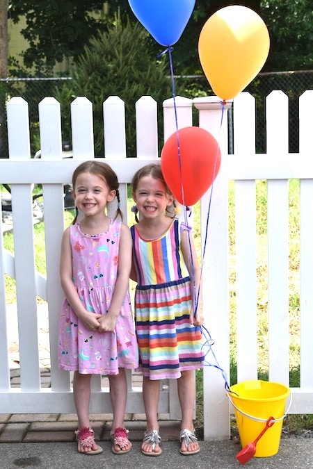 twin 5 year old girls standing in front of white picket fence with balloons embrace their individuality