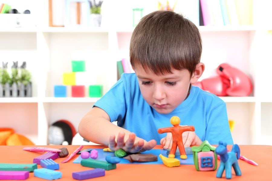 boy playing with toys at a table occupational therapy