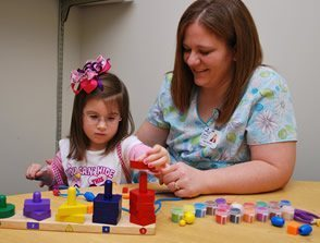 woman helping girl play with sensory toys at a table occupational therapy