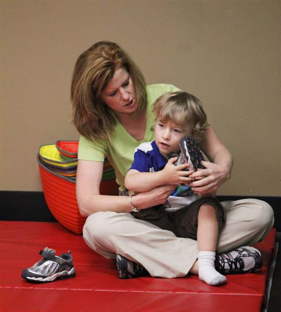 occupational therapist with child on a mat