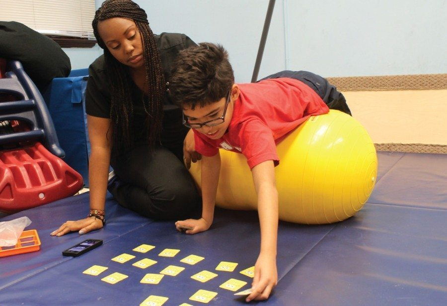 occupational therapist with boy laying on an exercise ball and playing a card game on a mat