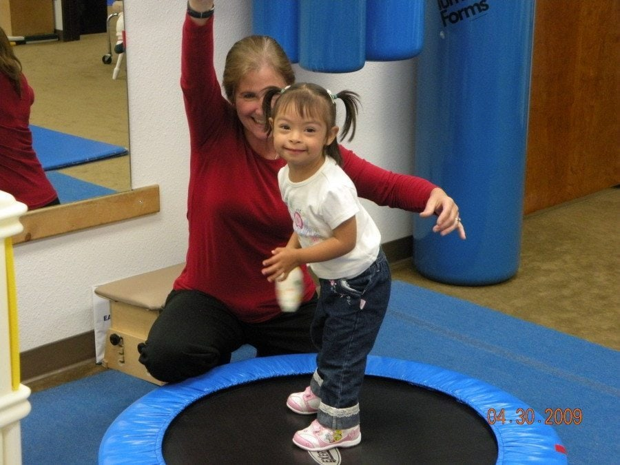 therapist with girl on trampoline occupational therapy