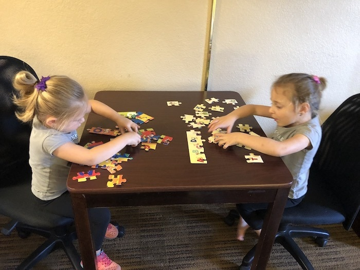 two girls playing a puzzle in a hotel evacuating