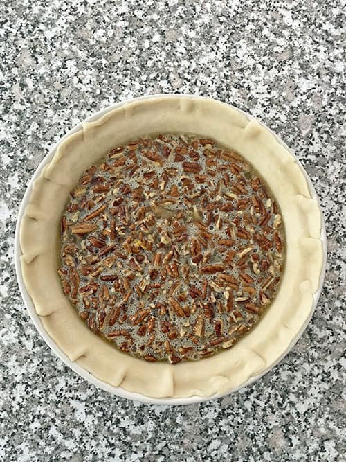 unbaked ingredients in a pie crust to make pecan pie