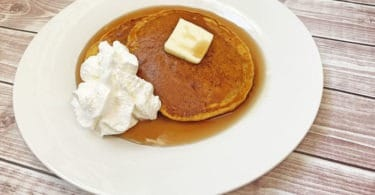 pumpkin pancakes with whipped cream butter and syrup on a plate