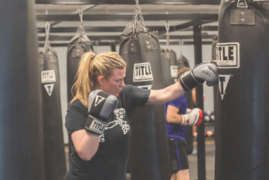 woman hitting a punching bag Reclaiming Yourself After Twins