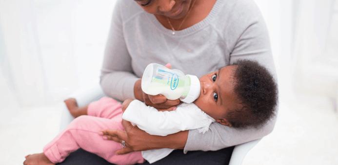woman feeding a baby a bottle feeding a breastfed baby