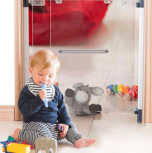baby with spoon in mouth sitting on the floor in front of clear baby gate baby proofing