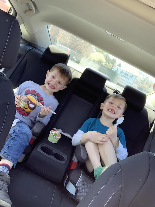 navigating twin boys in back seat of car eating ice cream