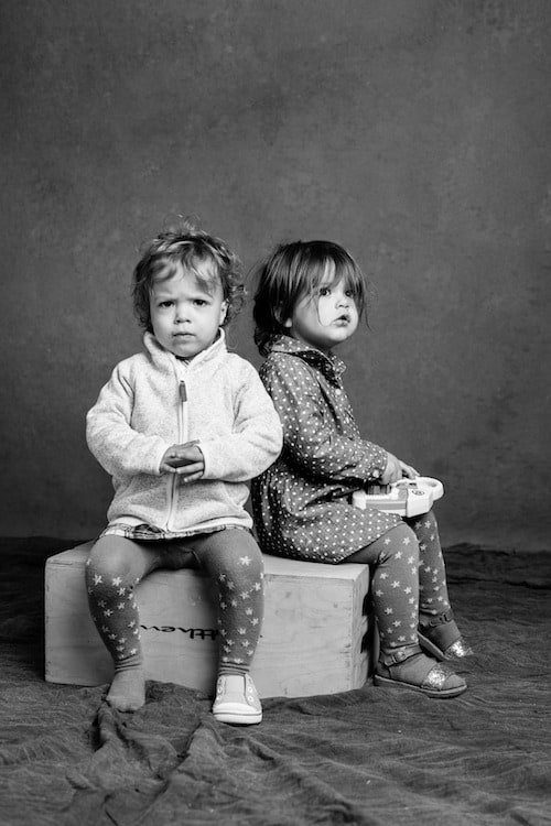 twin toddlers sitting on a box in black and white