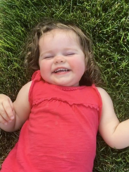 girl in grass smiling strong-willed child