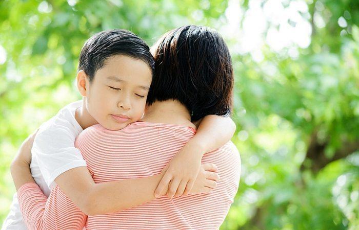 boy hugging mom woman
