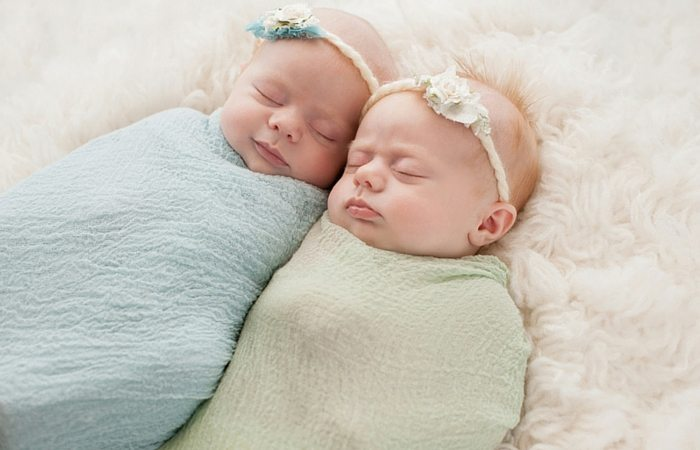 Newborn twin girls in blankets
