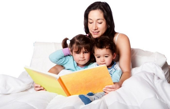 mom reading to kids in bed