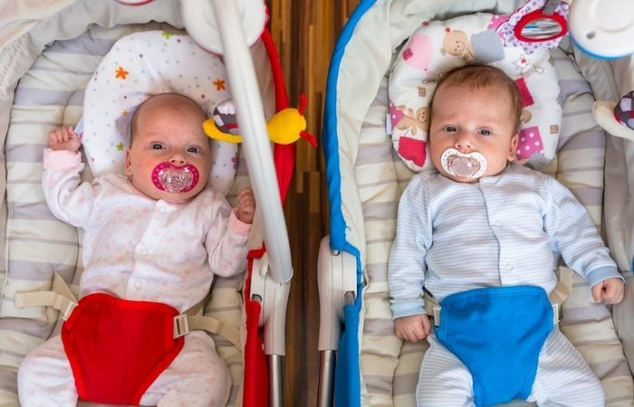 infant twins sittingin bouncy seats with pacifiers