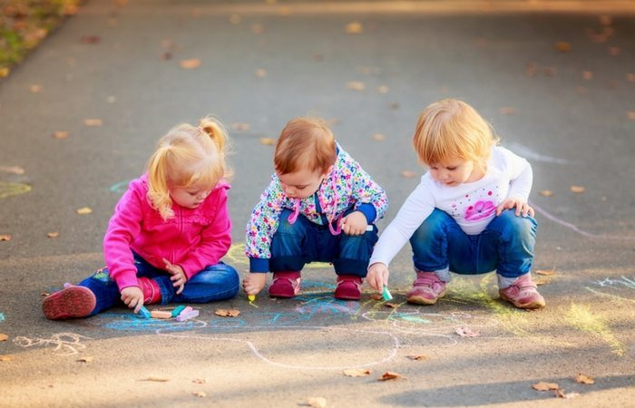 3 toddlers drawing with chalk outisde on sidewalk