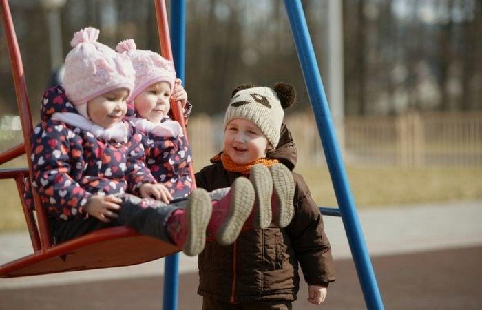 boy pushing twin girls on swing