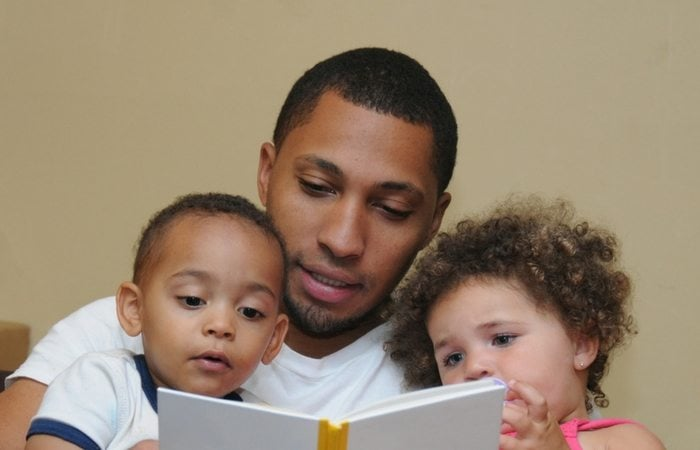Dad reading to twins