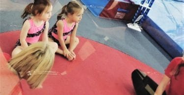twin girls sitting on mat at gymnastics class after-school activities